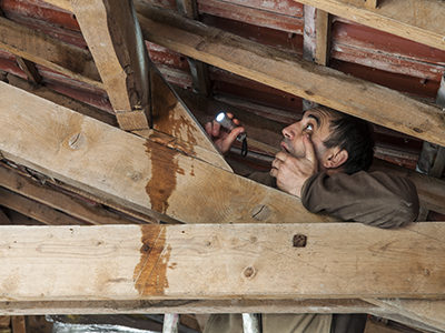 Plumber catching a water leak from the attic