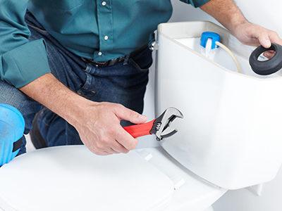 Plumber fixing broken toilet