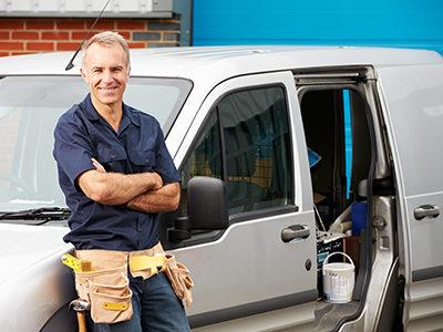 Plumber standing in front of his work van