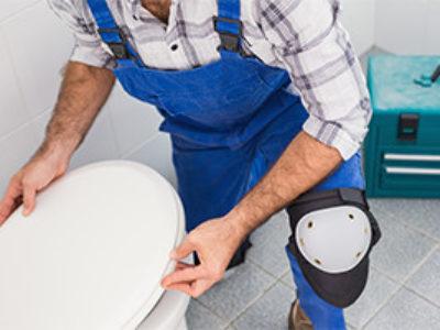 Plumber-making-repairs-to-toilet