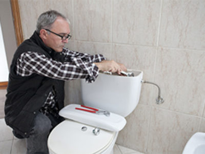 Plumber-working-on-toilet